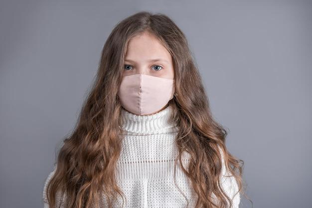 Portret van een jong aantrekkelijk meisje met blond lang stromend haar in een witte trui in medisch beschermend masker op een grijze studioachtergrond. plaats voor tekst. kopieer ruimte.