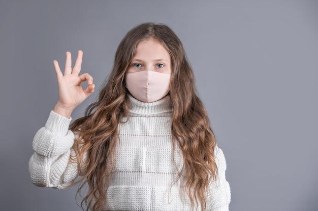 Portret van een jong aantrekkelijk meisje met blond lang stromend haar in een witte trui in medische beschermend masker vertoont goed teken