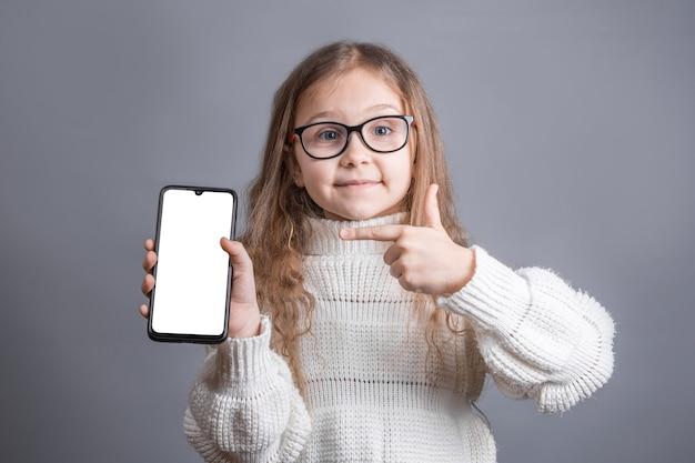 Portret van een jong aantrekkelijk meisje met blond lang stromend haar in een witte truigreep toont een mobiele telefoon