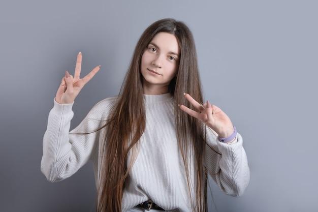 Portret van een jong aantrekkelijk meisje met donker lang haar sgesture v-teken voor overwinning of vredesteken