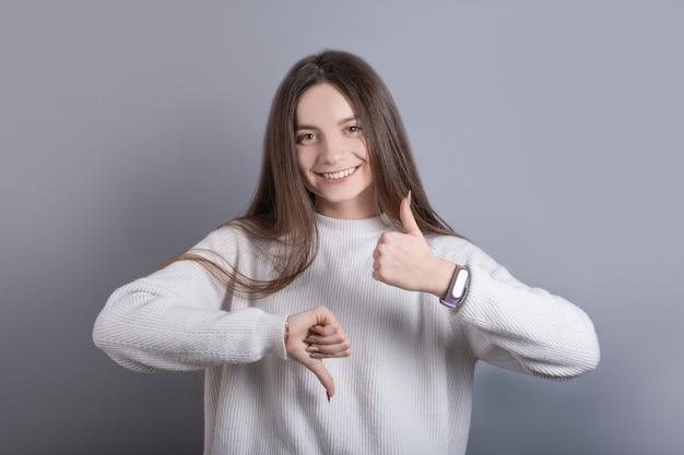 Portret van een jong aantrekkelijk meisje met donker lang haar toont duim omhoog of omlaag, goed of slecht op een grijze studioachtergrond. plaats voor tekst.