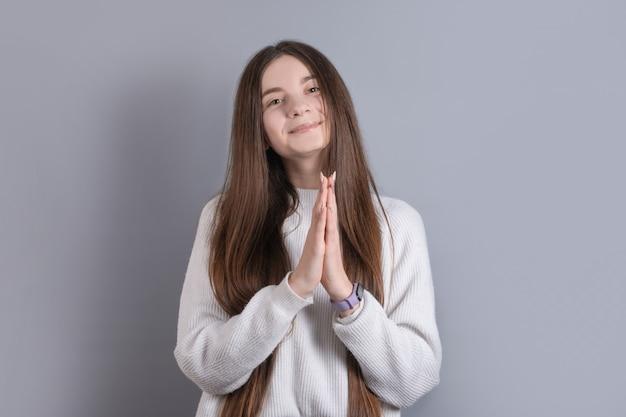 Portret van een jong aantrekkelijk meisje met donker lang haar waarin de handpalmen naar elkaar toe zijn gevouwen om iets op een grijze studioachtergrond te vragen. plaats voor tekst.