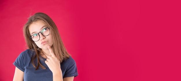 Portret van een jong aantrekkelijk meisje met een bril die haar kin vasthoudt en zijwaarts kijkt op een roodroze achtergrond.