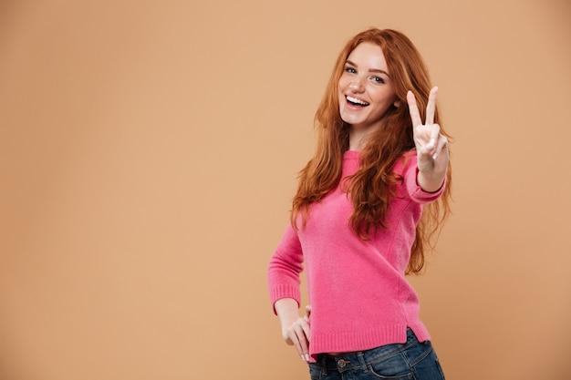 Portret van een jong aantrekkelijk roodharigemeisje met het gebaar van de overwinningshand