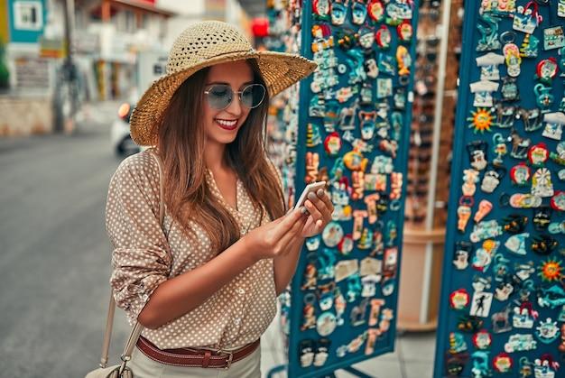 Portret van een jong aantrekkelijk toeristenmeisje in een strohoed, blouse en zonnebril, die rond de stadsmarkt loopt en magneten koopt. het concept van toerisme, reizen.