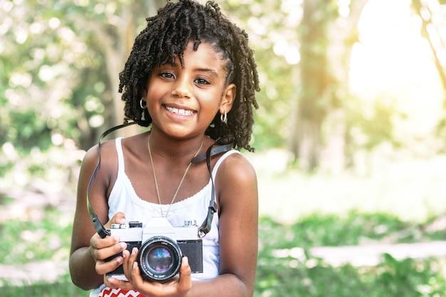 Portret van een jong afrikaans-amerikaans peutermeisje dat een oude camera vasthoudt en naar de camera kijkt