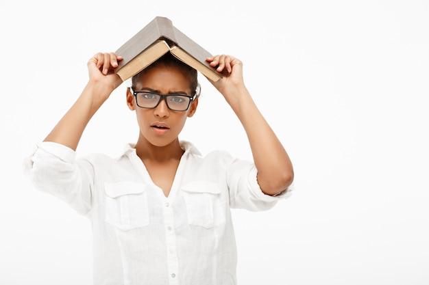 Portret van een jong afrikaans meisje met boek over witte muur