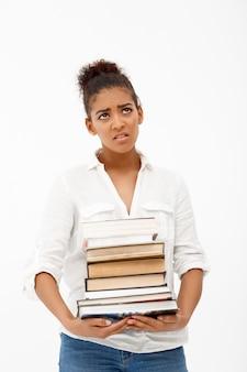 Portret van een jong afrikaans meisje met boeken over witte muur