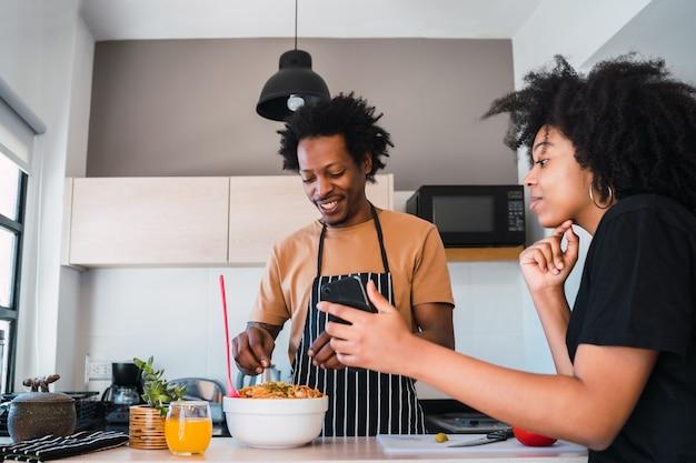 Portret van een jong afro paar samen koken en het gebruik van mobiele telefoon in de keuken thuis.