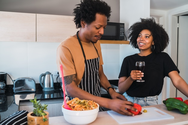 Portret van een jong afro paar samen koken in de keuken thuis. relatie-, kook- en levensstijlconcept.