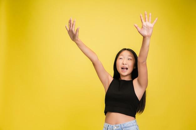 Portret van een jong aziatisch meisje dat op geel wordt geïsoleerd