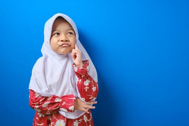 Portret van een jong aziatisch moslimmeisje zag er gelukkig uit, dacht na en keek omhoog, met een goed idee. half lichaamsportret tegen blauwe achtergrond met kopieerruimte