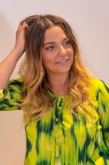 Portret van een jong blond kaukasisch meisje met kleine vlechten en een zomeroutfit met een geel en groen t-shirt