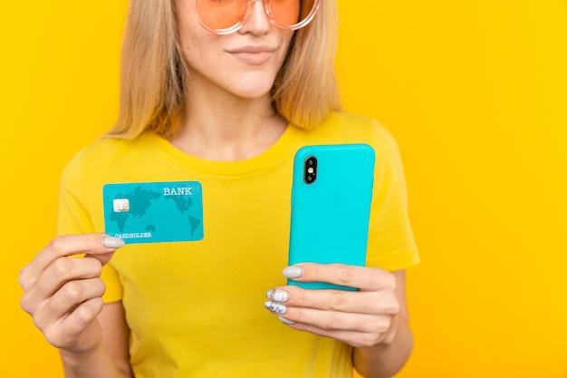 Portret van een jong blond meisje dat plastic creditcard toont tijdens het gebruik van mobiele telefoon geïsoleerd op gele achtergrond.