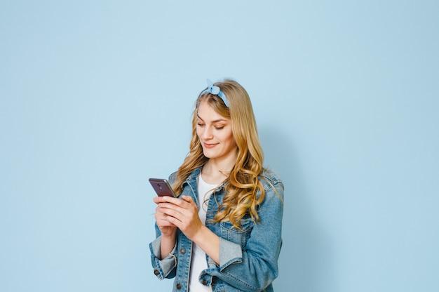 Portret van een jong blond meisje gelukkig waarom zij in haar mobiele telefoon ziet die over blauwe achtergrond wordt geïsoleerd