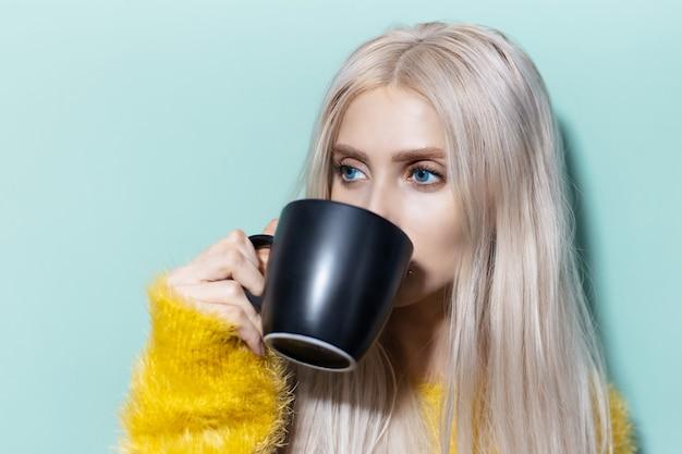 Portret van een jong blond meisje met blauwe ogen, het drinken van thee uit zwarte kop van achtergrond van aqua menthe kleur.