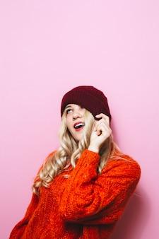 Portret van een jong blondemeisje dat een glb draagt en is gekleed in een rode sweater en manierbewegingen over roze muur toont