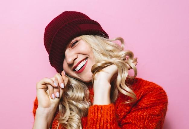 Portret van een jong blondemeisje dat een pet draagt en is gekleed in een rode sweater en modebewegingen over pinkwall toont