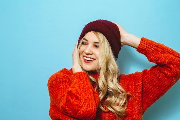 Portret van een jong blondemeisje die een glb dragen en is gekleed in een rode sweater en manierbewegingen over blauwe muur tonen