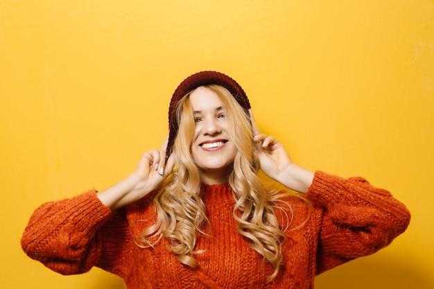 Portret van een jong blondemeisje die een glb dragen en is gekleed in een rode sweater en manierbewegingen over gele muur tonen