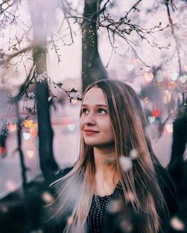 Portret van een jong blondemeisje met vage achtergrond met bokeh van harten