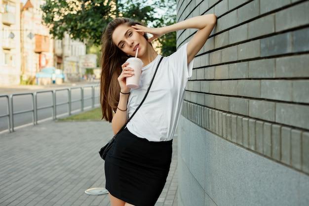 Portret van een jong donkerbruin meisje in een witte milkshake van de t-shirtholding