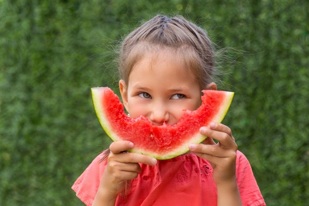 Portret van een jong donkerbruin meisje met watermeloen