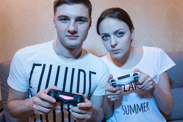 Portret van een jong en aantrekkelijk stel jongen en meisje die een videogame spelen, zittend op de bank voor de tv thuis in een ontspannen sfeer