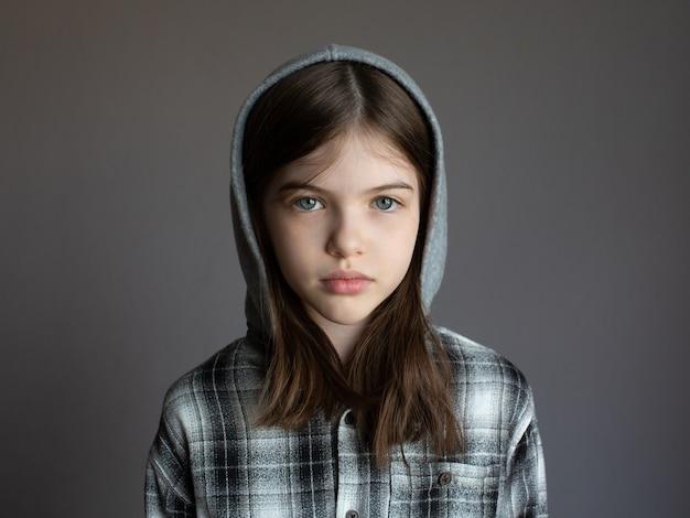 Portret van een jong ernstig meisje in een hoodie op donker