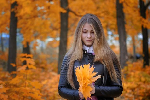 Portret van een jong europees meisje in een herfstpark met geel gebladerte
