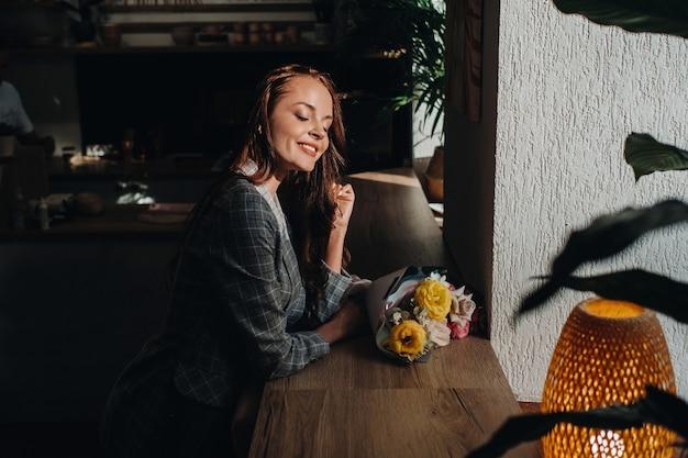 Portret van een jong europees meisje met lang haar in een café met een boeket dat bij het raam staat, een lang meisje in een jas met lang haar in een café te wachten.