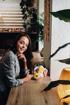Portret van een jong europees meisje met lang haar in een café met een boeket staande bij het raam, een lang meisje in een jas met lang haar in een café te wachten.