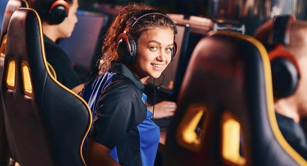 Portret van een jong gelukkig gemengd rasmeisje, vrouwelijke gamer met een koptelefoon die naar de camera glimlacht tijdens het spelen van online videogames, die deelneemt aan een esport-toernooi. cybersport professioneel team