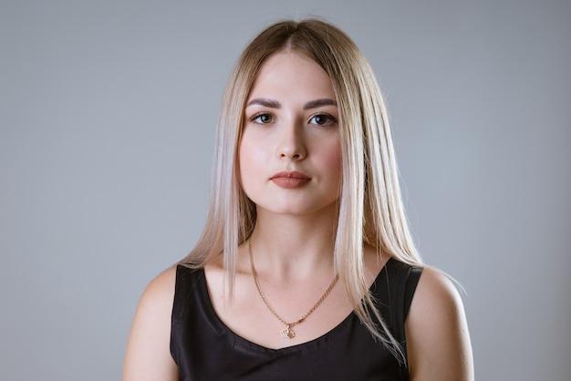 Portret van een jong gelukkig kaukasisch meisje in een zwart t-shirt dat zich voordeed op een lichte muur