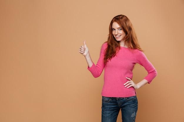 Portret van een jong gelukkig roodharigemeisje die gelukkig met omhoog duimen kijken