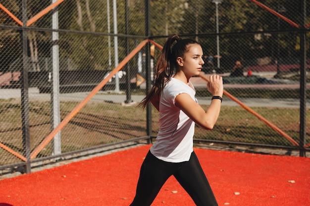 Portret van een jong geschikt wijfje dat de routine van de ochtendsport in een sportpark doet.