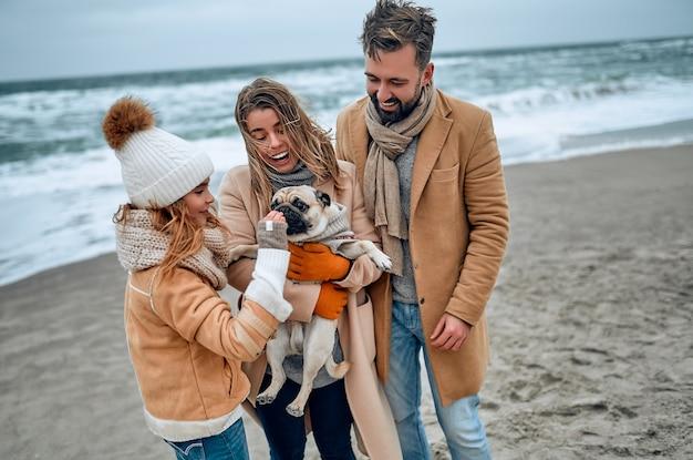 Portret van een jong getrouwd stel en hun schattige dochter die in de winter plezier hebben met een hond op het strand en in de winter warme kleren en sjaals dragen.
