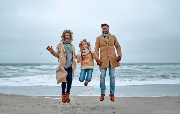 Portret van een jong getrouwd stel en hun schattige dochter die in de winter plezier hebben op het strand met warme kleren en sjaals.