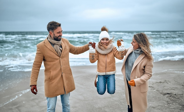 Portret van een jong getrouwd stel en hun schattige dochter die zich in de winter op het strand vermaken en in de winter warme kleren en sjaals dragen.