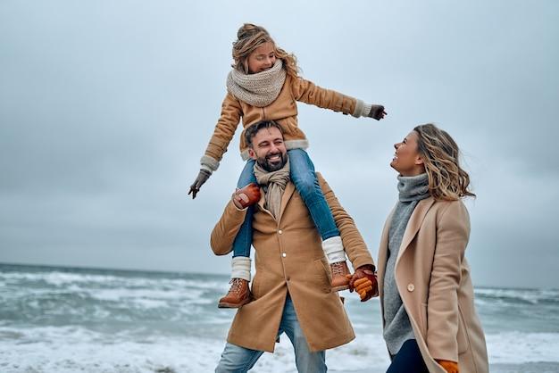 Portret van een jong getrouwd stel en hun schattige dochter die zich in de winter op het strand vermaken.