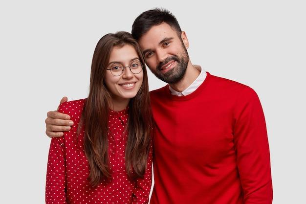 Portret van een jong gezin europees echtpaar draagt rode kleren, poseert voor het maken van een gemeenschappelijke foto, heeft goede relaties