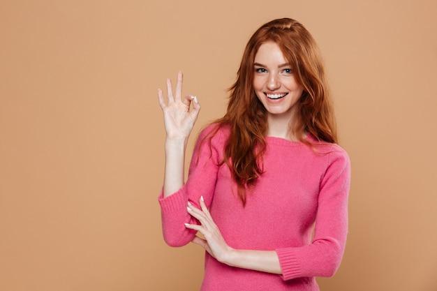 Portret van een jong glimlachend roodharigemeisje die makend het ok gebaar kijken