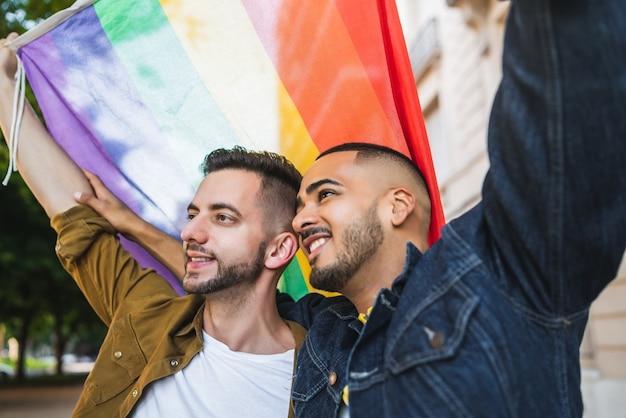 Portret van een jong homopaar omarmen en hun liefde met regenboogvlag tonen op straat. lgbt en liefde concept.