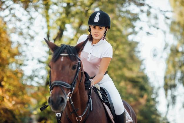 Portret van een jong jockeymeisje dat een bruin paard berijdt in de herfstbos.