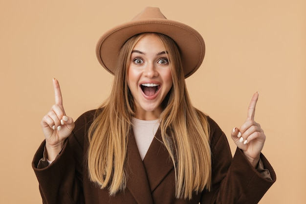 Portret van een jong kaukasisch meisje met een hoed en jas die lacht en met de vingers naar boven wijst naar copyspace geïsoleerd op beige