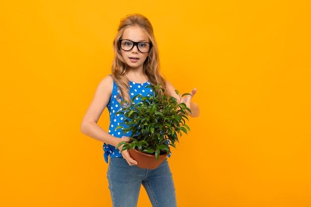 Portret van een jong kaukasisch meisje met lang blond haar in zwarte glazen bedrijf plant
