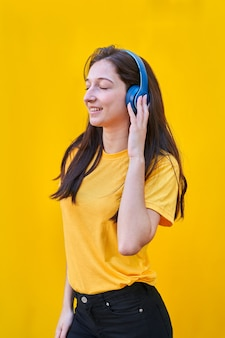 Portret van een jong kaukasisch meisje met lang bruin haar, geel t-shirt en zwarte spijkerbroek, luistert naar muziek met haar blauwe koptelefoon.