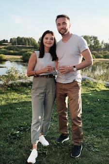 Portret van een jong koppel elkaar omhelzen en glimlachen terwijl ze buiten staan