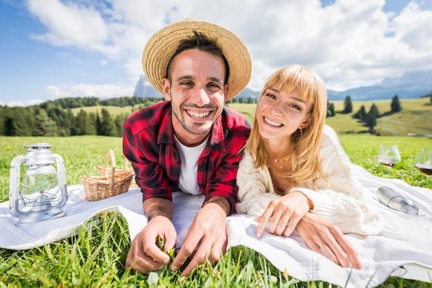 Portret van een jong koppel in liefde die picknick doet die de dolomieten van de alpen bezoeken