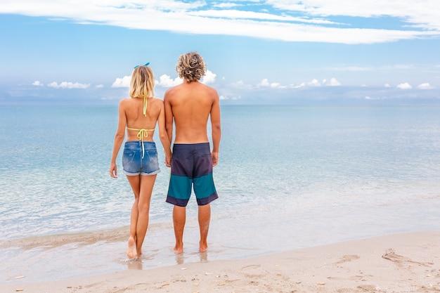 Portret van een jong koppel in liefde omarmen op strand en genieten van tijd samen zijn. achteraanzicht van jonge gelukkige paar op tropisch strand. huwelijksreis concept